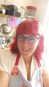 The FullyStuffedGeek herself with bright red hair and blue butterfly glasses, standing in her kitchen.